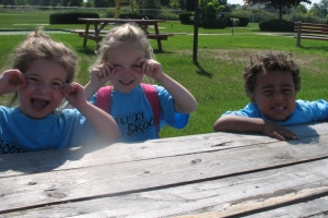 Smiling kids on picnic tables